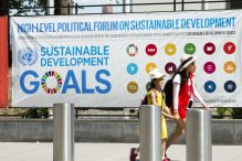 Poster for HLPF, 2 schoolgirls walk by in front of it