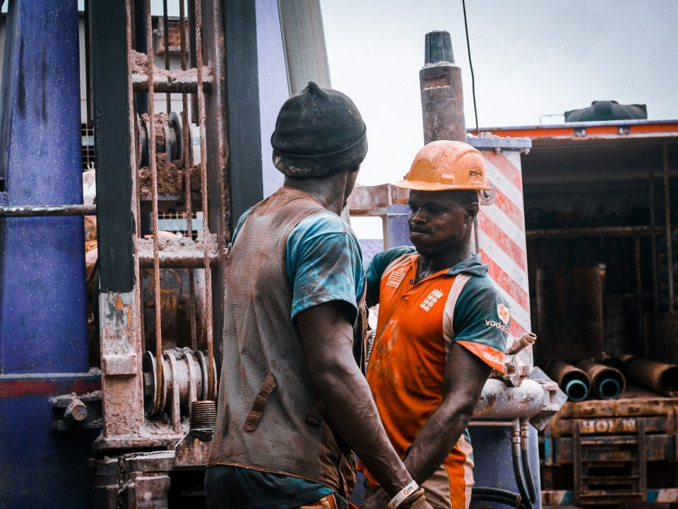 workers standing beside drilling machine